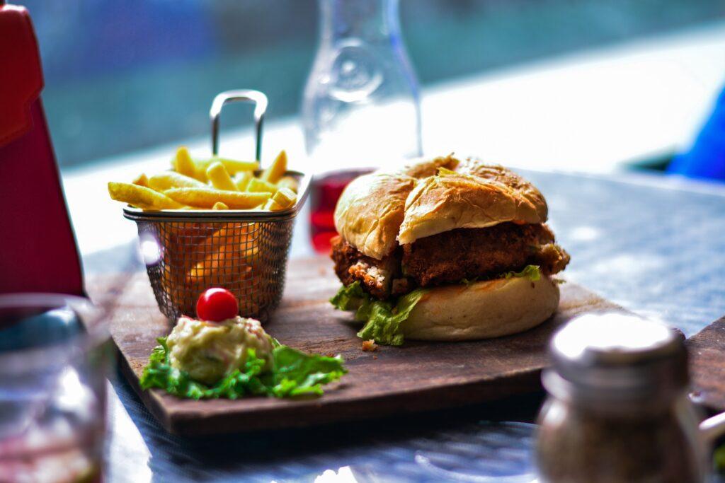 Ein Burger angerichtet auf einem Holzbrett mit Pommes Frites und einer Sauce